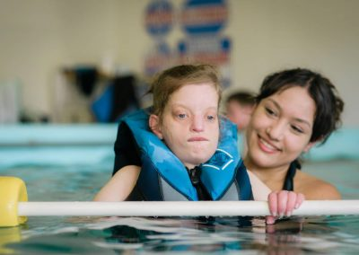 Woman helping young Hillside resident in the pool