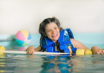Young woman with disabilities floating in the pool