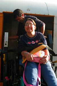 Female at resident in wheelchair smiling at camera while volunteer helps