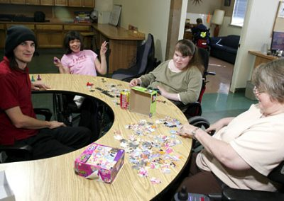 Hillside residents putting together a puzzle and smiling