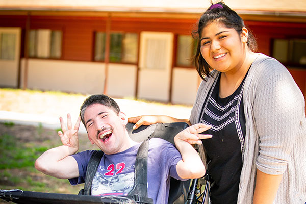 Young woman with male resident in wheelchair laughing